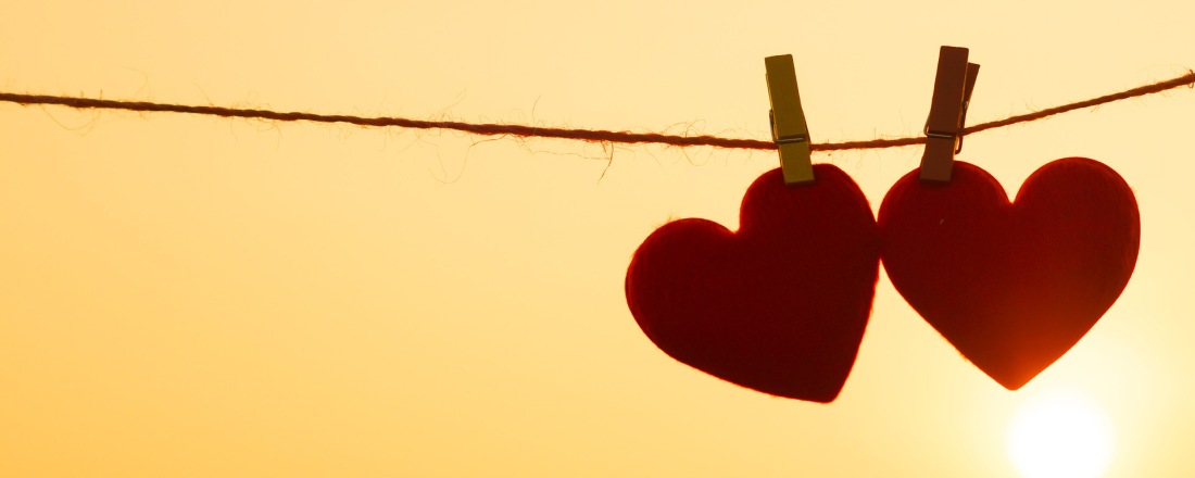 Two red paper hearts juxtaposed against the yellow sun