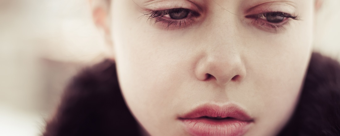 Young female's face close up. Her eyes are showing sadness, sorrow and solitude
