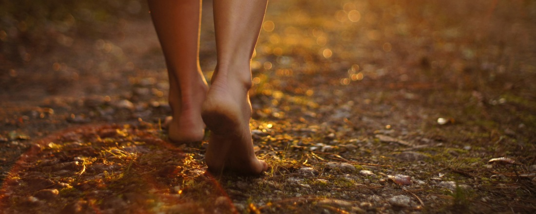 Bare foot woman walking away early in an early autumn morning.