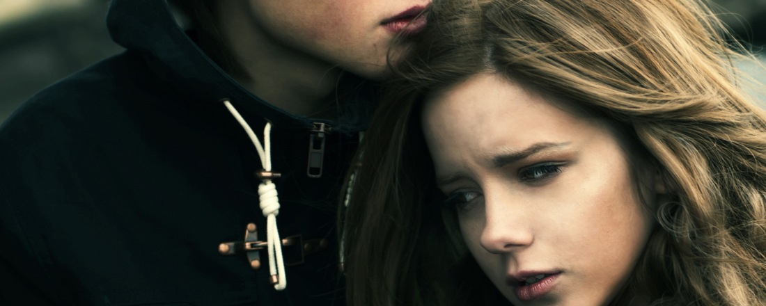 Young heterosexual couple hugging side by side. She is resting her head over his chest. Her eyes reflect both sadness and disbelieve.