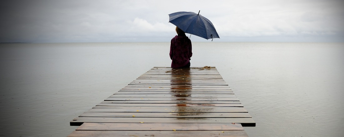 Woman seating at the end of a wooden dock overlooking a big lake. She is holding an umbrella over her right shoulder.