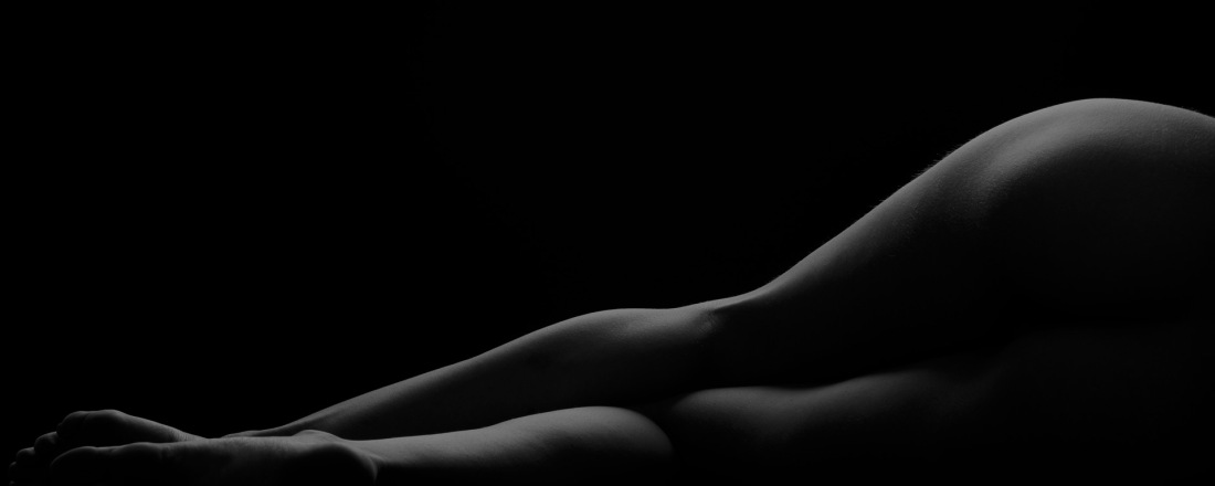 Black and White Photo. Female legs and hips laying on the right side. The light outlines the silhouette.