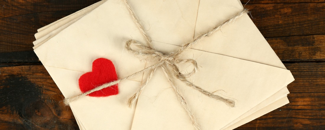 A group of envelopes. Tied up and decorated with one heart.