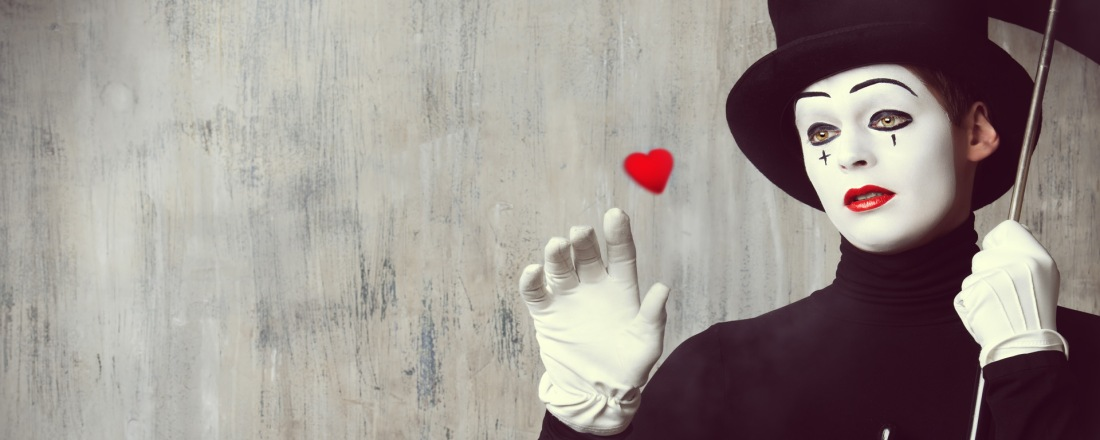 Mime looking at a small heart that is floating in front of him.