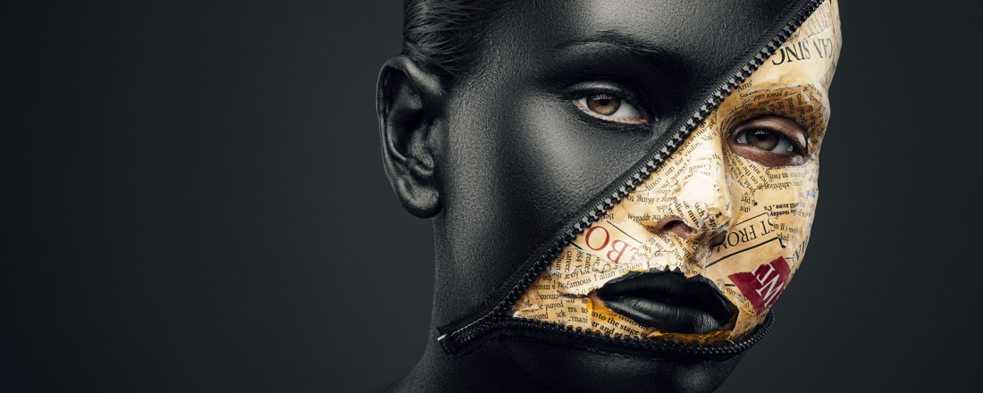 Creative Makeup: Close up to a female face painted in Black, a zipper tapped across her face is open, yellow newspaper pieces had been glued inside the zippered area. She is looking straight at you.