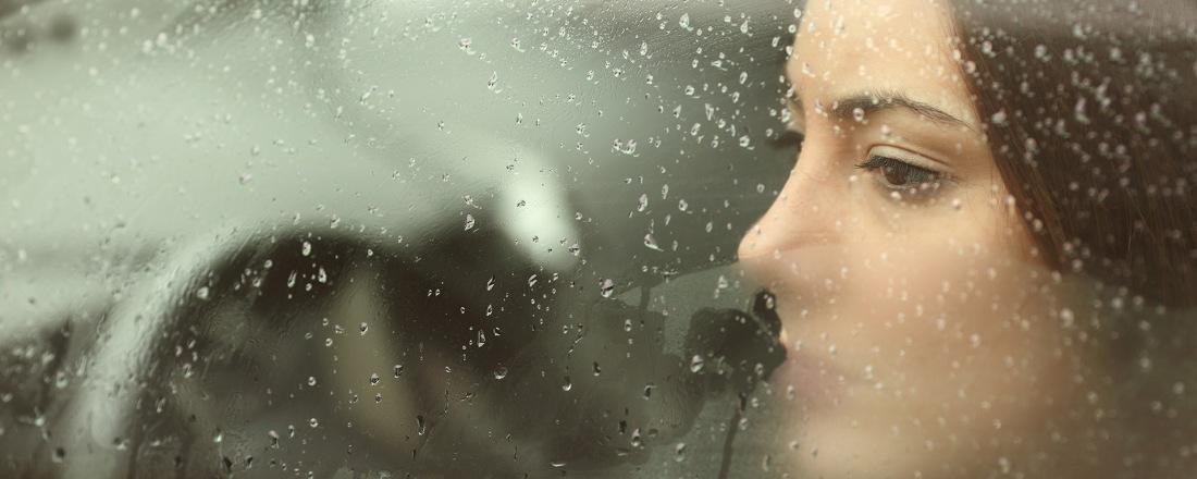 Mujer sentada en su carro durante una mañana lluviosa. No esta manejando. Esta observando a alguien que esta lejos.