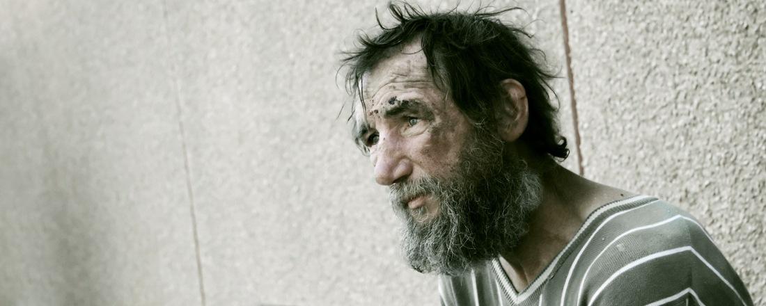 Habitante de la calle. Hombre, delgado, despeinado, sucio y triste sentado en alguna calle.