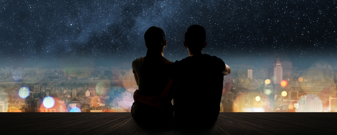 Couple seating at the edge of a terrace overlooking the city. Night time.