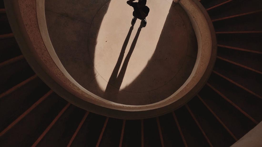 Escaleras en espiral. Una personal esta en medio de ellas, mirando hacia una puerte