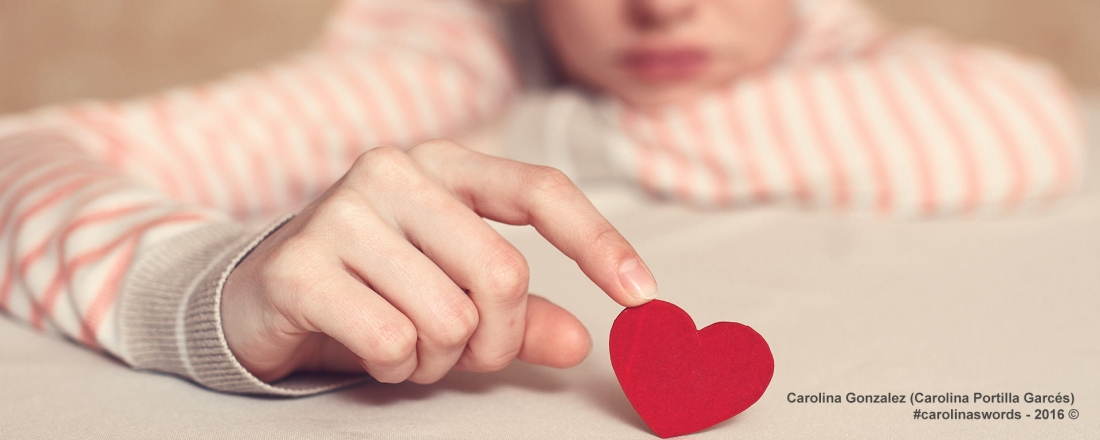 Young female out of focus playing with a paper red heart. She is pensive, maybe sad.