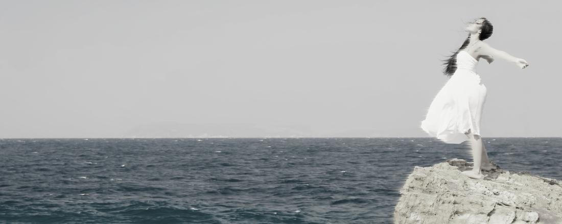 Mujer a la orilla del mar, parada sobre una roca, con sus brazos extendidos hacia atrás, y la mirada hacia el cielo