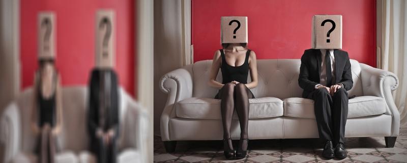 Pareja sentada en un sofa, con cajas en la cabeza. Cada caja tiene un signo de interrogación.